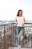Mooie dame die van het weer en van een photosession genieten die plaats op het balkon van haar hotel hebben Royalty-vrije Stock Foto