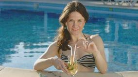 Mooie dame die van lange drank in zwembad genieten, die bij nok glimlachen stock video