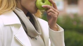 Mooie dame die verse groene appel gezonde snacks bijten tijdens lunchtijd, voeding stock videobeelden