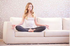 Mooie dame die yoga op bank doen stock afbeelding