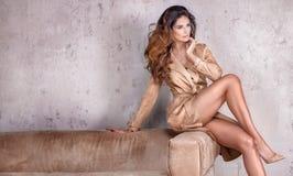 Mooie dame met lang krullend kapsel en het slanke benen stellen Royalty-vrije Stock Fotografie