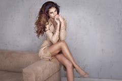 Mooie dame met lang krullend kapsel en het slanke benen stellen Royalty-vrije Stock Foto's