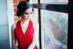 Mooie dame in rode kleding met een avondsamenstelling stock afbeeldingen