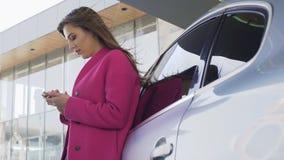Mooie dame in roze laag die zich dichtbij automobiel bevinden en op smartphone scrollen stock video