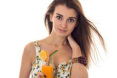Mooie dame in sarafan met bloemenpatroon die de camera en dranken de oranje die cocktail bekijken op witte achtergrond wordt geïs Stock Fotografie