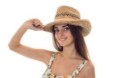 Mooie dame in strohoed en sarafan met bloemenpatroon die die de camera en glimlachen bekijken op witte achtergrond wordt geïsolee Stock Foto