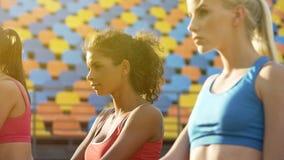 Mooie dames die bij stadion, geest van de concurrentie, multiraciaal team opleiden stock foto's