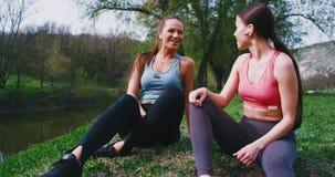 Mooie dames die met grote glimlach na een harde trainingoefeningen op gras en het glimlachen het babbelen gaan zitten terwijl stock video