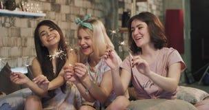 Mooie dames die in pyjama's van de tijd genieten samen bij sleepovernacht groot glimlachen en gebruiken fonkelend vuurwerk stock videobeelden