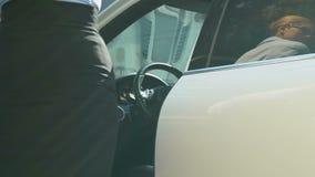 Mooie damewerkgever die van dure auto weggaan en aan bureau lopen stock videobeelden