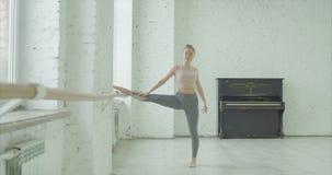 Mooie danser die bij staaf in balletstudio opwarmen stock video
