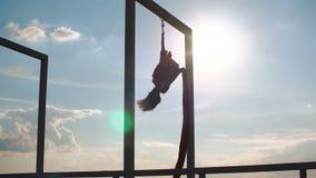 Mooie danser op luchtzijde De jonge sexy vrouw voert acrobatische stunts op het dak bij zonsondergang uit stock videobeelden