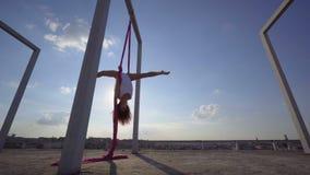 Mooie danser op luchtzijde De jonge sexy vrouw voert acrobatische stunts op het dak tegen hemel met wolken uit stock video