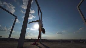 Mooie danser op luchtzijde De jonge sexy vrouw voert acrobatische stunts op het dak tegen hemel met wolken uit stock videobeelden