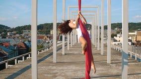 Mooie danser op luchtzijde De jonge sexy vrouw voert acrobatische stunts op het dak tegen hemel met wolken uit stock footage