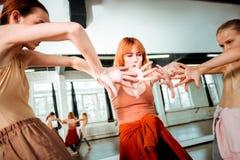 Mooie dansleraar die met rood haar bewegingen verklaren aan haar studenten stock afbeelding