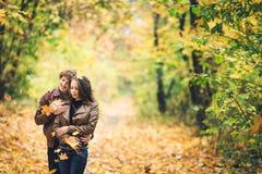 Mooie de herfststeeg van esdoorns Het houdende van paar omhelst en de gele bladeren vallen op hen stock fotografie