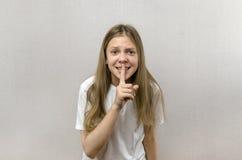 Mooie de holdingsvinger van het blondemeisje dichtbij lippen stil en shh gebaar Close-up royalty-vrije stock foto