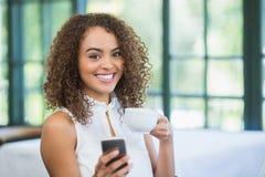 Mooie de koffiekop van de vrouwenholding en het gebruiken van mobiele telefoon Royalty-vrije Stock Afbeeldingen