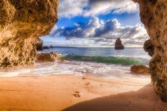 Mooie de meningshorizon van de Atlantische Oceaan met zandige strand, rotsen en golven bij zonsopgang Algarve, Portugal Stock Afbeelding