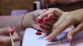 Mooie de vrouwenringvinger van de manicure hoofdholding in hand en het aanpassen bergkristallen op spijker door speciaal hulpmidd stock footage