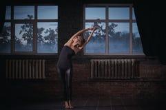 Mooie de yogaasana Tiriaka Tadasana van vrouwenpraktijken in de donkere zaal Royalty-vrije Stock Foto's