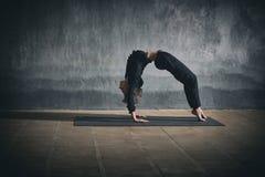 Mooie de yogaasana Urdhva die Dhanurasana van vrouwenpraktijken backbend - omhoog boog onder ogen zien stel in de donkere zaal Royalty-vrije Stock Afbeeldingen