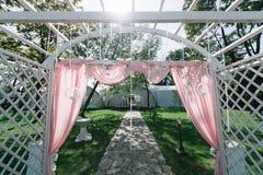 Mooie decoratie voor de ceremonie van het de zomerhuwelijk in openlucht Huwelijksboog die van lichte doek en witte en roze bloeme Royalty-vrije Stock Afbeeldingen