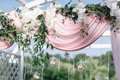 Mooie decoratie voor de ceremonie van het de zomerhuwelijk in openlucht Huwelijksboog die van lichte doek en witte en roze bloeme Royalty-vrije Stock Afbeelding