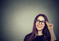 Mooie denkende vrouw die in glazen omhoog op grijze achtergrond met exemplaarruimte kijken royalty-vrije stock afbeelding
