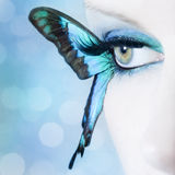 Mooie dichte omhooggaand van het vrouwenoog met vlindervleugels stock fotografie