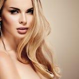 Mooie dichte omhooggaande het portret jonge studio van het vrouwengezicht met krullend lang blondehaar Royalty-vrije Stock Foto's