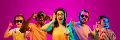 Mooie die jongeren in neonlicht op roze studioachtergrond wordt ge?soleerd stock afbeeldingen