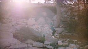 Mooie die lensgloed van mooie lokale meisje wandeling wordt geschoten, neer lopend op stenen die de bos langzame motie van Yosemi stock video