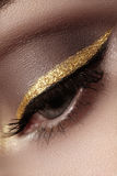 Mooie die macro van vrouwelijk oog met plechtige make-up wordt geschoten Perfecte vorm van wenkbrauwen, eyeliner en vrij gouden l Royalty-vrije Stock Afbeeldingen