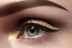 Mooie die macro van vrouwelijk oog met plechtige make-up wordt geschoten Perfecte vorm van wenkbrauwen, eyeliner en vrij gouden l Stock Afbeeldingen
