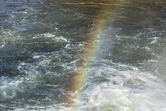 Mooie die mening van een regenboog in het water wordt weerspiegeld stock foto's