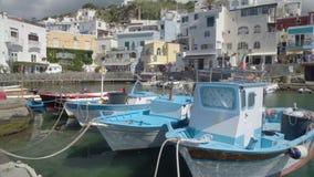 Mooie die vissersboten dichtbij kade in toevluchtstad worden geparkeerd, mening van gebouwen stock video