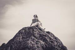 Mooie die vrouw bovenop een berg wordt gezeten Royalty-vrije Stock Foto's