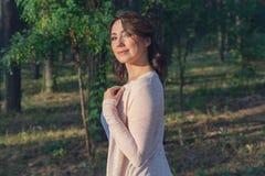 Mooie die vrouw door de zon in het park wordt aangestoken Royalty-vrije Stock Afbeelding