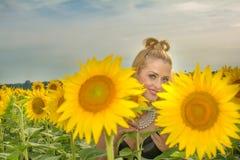 Mooie die vrouw door zonnebloemen wordt omringd Royalty-vrije Stock Fotografie