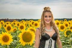 Mooie die vrouw door zonnebloemen wordt omringd Royalty-vrije Stock Foto