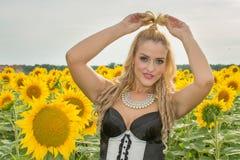 Mooie die vrouw door zonnebloemen wordt omringd Royalty-vrije Stock Foto's