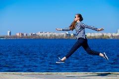 Mooie die vrouw langs pijler door overzees in zonnige dag in werking wordt gesteld royalty-vrije stock foto