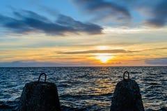 Mooie die zonsondergang tussen rotsen bij Oostzee wordt ontworpen Stock Fotografie