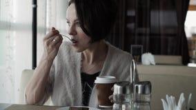 Mooie donkerbruin drinkt koffie van een kop en het eten van kaastaart stock videobeelden