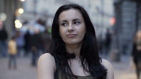 Mooie donkerbruine bedrijfsvrouw die bepaling met mensen uitdrukken die op straatachtergrond lopen stock video