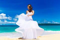 Mooie donkerbruine bruid in witte huwelijkskleding met grote lang wh Stock Afbeelding