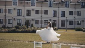 Mooie donkerbruine buiten en bruid blijven die zich omdraaien De vrouw in witte huwelijkskleding geniet van de dag van ceremonie stock videobeelden