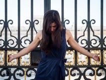 Mooie donkerbruine die vrouw op de poort van een paleis wordt gekruisigd Stock Afbeeldingen